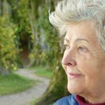 Older woman in deep thought looking at the countryside